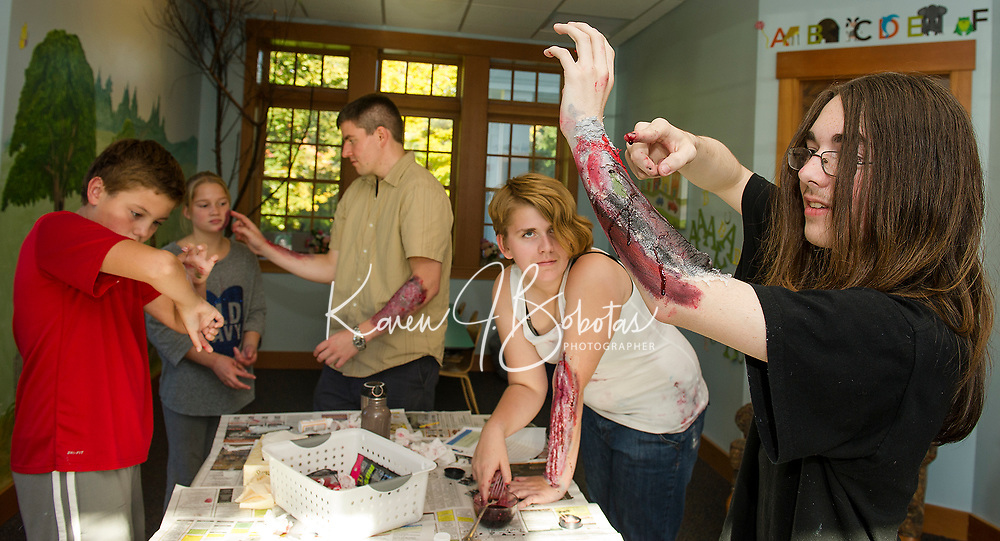 Tyler Morrisette, Alexa Smith, Mark Thomas and Lili Griggs work on their flesh wounds as Jack Brown adds some fresh blood to his arm during the Zombie Workshop at Gilford Library Thursday afternoon.   (Karen Bobotas/for the Laconia Daily Sun)