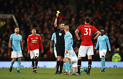 Manchester City's David Silva (centre right) is shown the yellow card by Match referee Michael Oliver