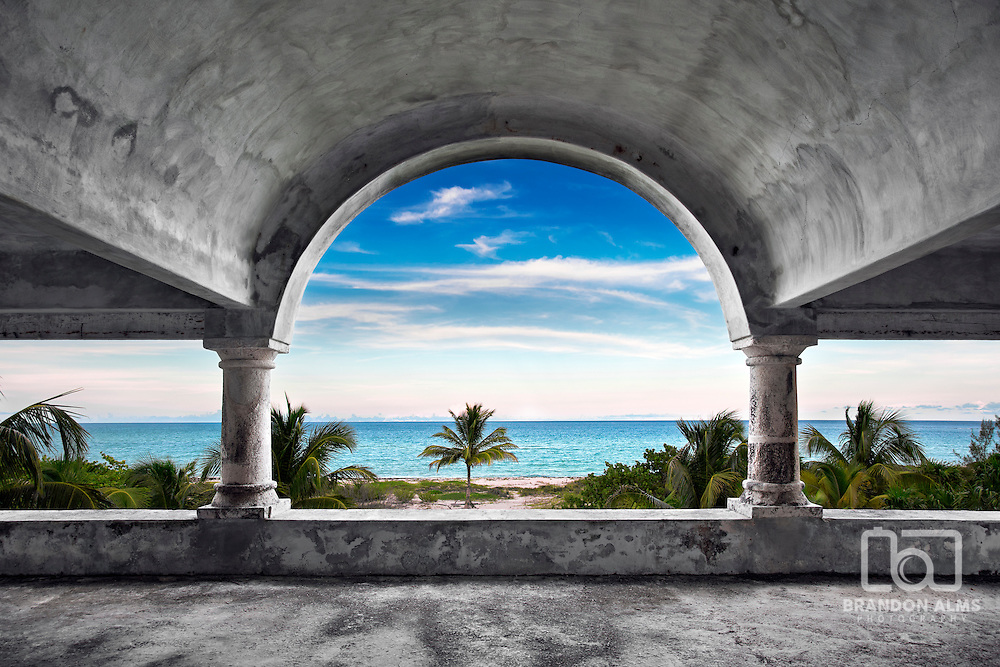 A beautiful view of the ocean from inside an old abandoned mansion.