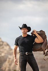 rugged cowboy holding a saddle on a mountain top