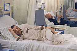 Patients lying in beds on hospital ward,