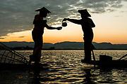 Myanmar, Shan state, Inle lake, two fishermen drinking tea at dusk