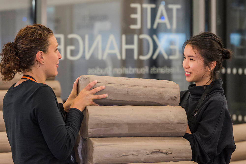 Students Flor Mendschein and Bridgette Chang collect some more raw clay - FACTORY: the seen and the unseen - an installation, in the form of a ceramics factory, by artist Clare Twomey. It is set up in the Blavatnik Building of the Tate Modern and launches the second year of Tate Exchange which, over 2017 and 2018, will focus on the theme of production.