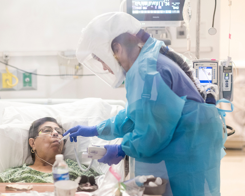 Nurse Cassie Barber (right) takes the temperature of Carmelita Martinez, a 75-year-old Salinas woman, inside a COVID-19 unit at Salinas Valley Memorial Hospital in Salinas, Calif. on Jan. 14, 2021. Days later, Martinez was moved to Comfort Care, a form of hospice to help at the end of life. Martinez died of COVID-19 on Jan. 23, 2021.