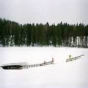 Three men going ice swimming after a sauna at the small lake of Vuorilampi, Jyvaskyla, Central Finland. Ice swimming takes place in a body of water with a frozen crust of ice, which requires a hole cutting in it.  In Finland, the ice swimming tradition has generally been connected with the sauna tradition and it is not seen as an ascetic or religious ritual, but as a way to cool off rapidly after staying in the sauna and as a stress relief.