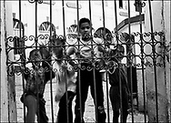 Children jump about at the gate to their schoolyard in Prizren, Kosovo.