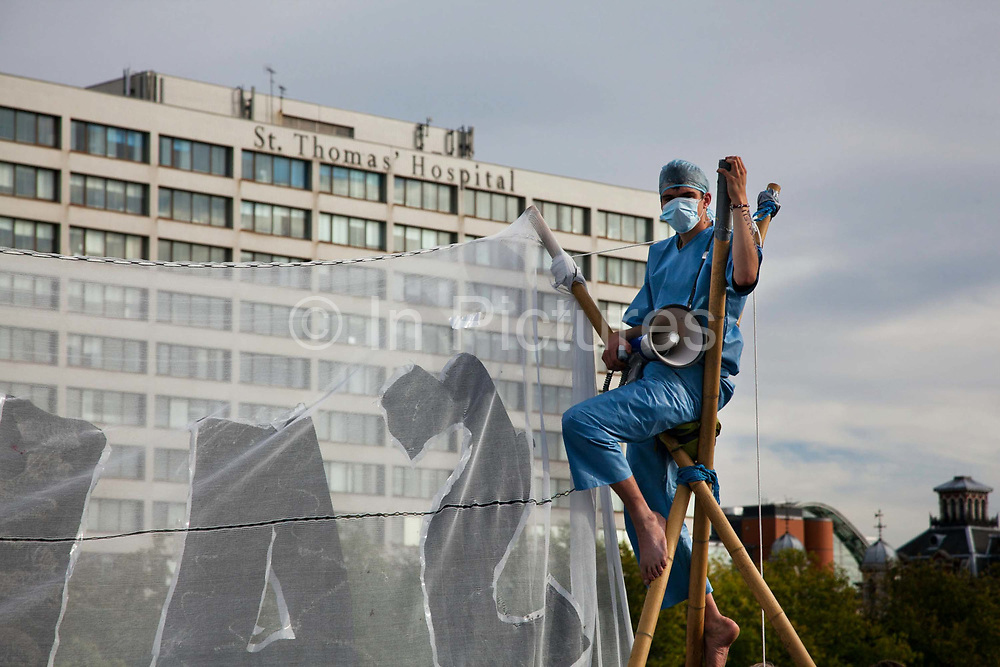 An activist dressed as a health worker sitting on top of one of the two tri-pods used to block the bridge.<br /> The Health and Care Bill has been passed by Parliament and is due to go to the House of Lords. In protest against the bill which aim to deconstruct and privatise large parts of the NHS UK Uncut activists together with health workers and trade unionists blocked the Westminster Bridge from 1pm til 5.30pm.