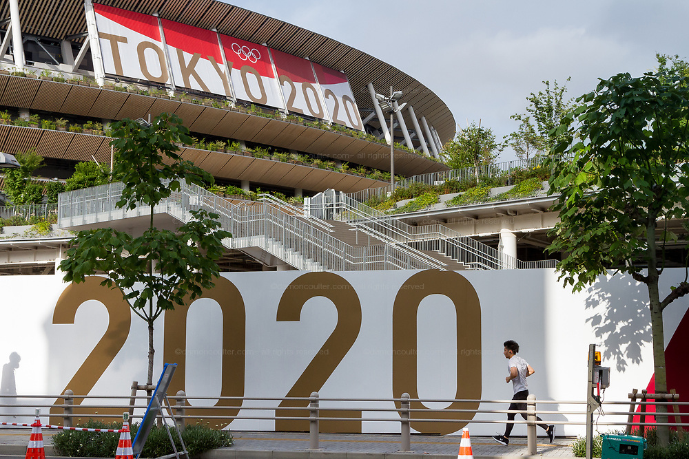 A jogger runs past large Tokyo 2020 signs around the National Olympic stadium, Gaiemmae, Tokyo, Japan. Saturday July 3rd 2021. The Tokyo Olympic Organising committee are planning to open the delayed Games on July 21st despite uncertainty on what measures to take to ensure safety for athletes, spectators and the local population in the continuing COVID-19 pandemic.