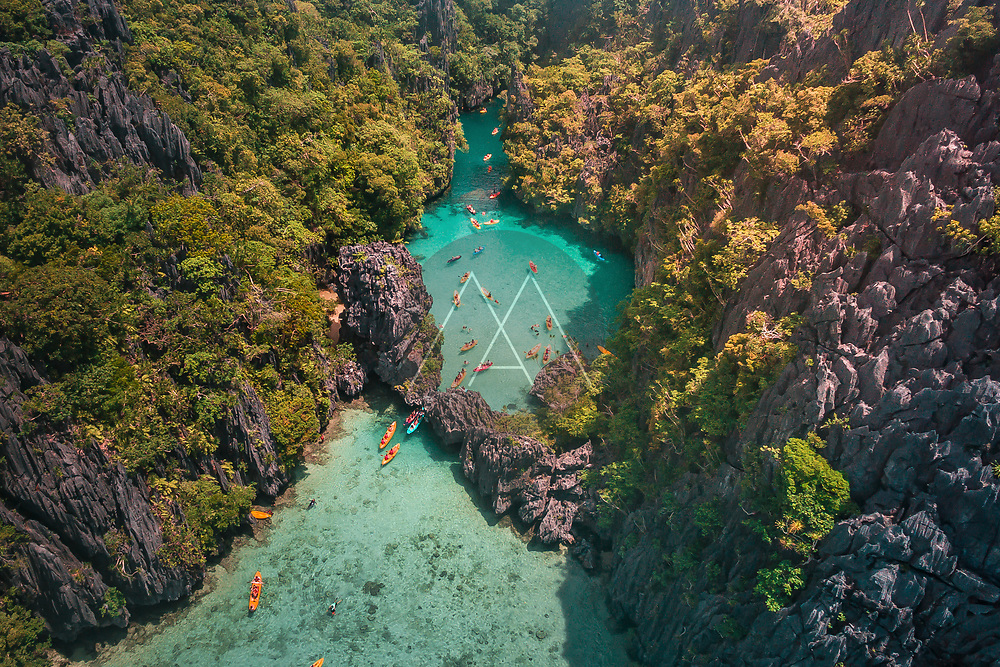 An aerial view of tourists kayaking going in and out in the Small Lagoon to Big Lagoon in Maniloc Island, El Nido, Palawan, Philippines.