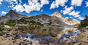 Sierra peaks reflect in Piute Lake on Piute Pass Trail, in John Muir Wilderness, Inyo National Forest, Mono County, California, USA. Hike to Piute Pass for 9.7 miles round trip with 2200 feet gain. Multiple overlapping photos were stitched to make this panorama.