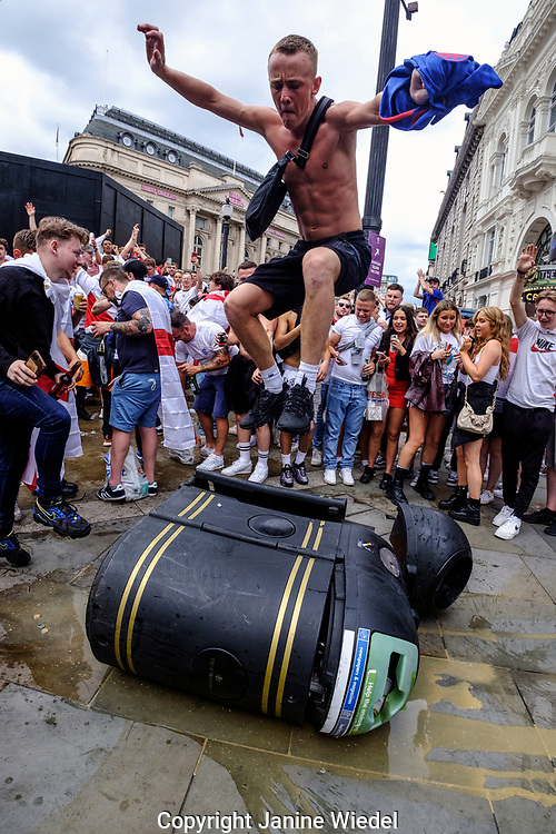 English Football fans vandalising garbage bin in Picadilli Circus, Central London, before the finals of football match against Italy.  England v Italy Euro 2020 final. 11 July 2021