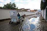 A horse and cart trap riding through a flooded street in an old Colonial town, Paraty, Rio de Janeiro, Brazil.