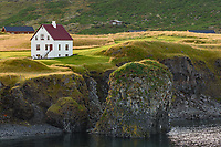 Golden sunlight illuminates a white seaside house in the Icelandic village of Arnarstapi.
