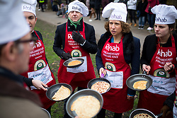 © Licensed to London News Pictures. 13/02/2018. London, UK. The Media team practise ahead of the Rehab Parliamentary Pancake Race 2018 in Victoria Tower Gardens. The Parliament Team - made up of MPs, Lords and Ladies - race in a relay against the Media Team - made up of reporters and presenters - whilst continuously flipping pancakes to celebrate Shrove Tuesday, also known as Pancake Day. Photo credit : Tom Nicholson/LNP