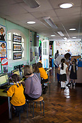 Inside a classroom at South Farnborough Infant School, Hampshire, UK.  One female teacher sits with some pupils who are working on computers. Another teacher bends down to talk to some children who have come to ask a question.