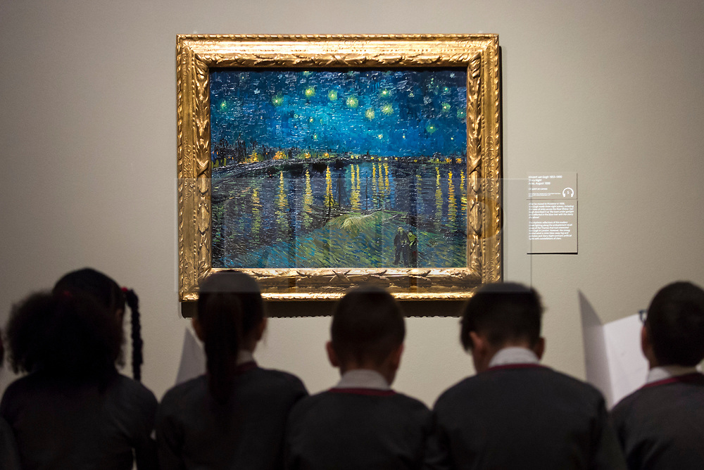 """© Licensed to London News Pictures. 25/03/2019. LONDON, UK. Pupils from Millbank Primary Academy view """"Starry Night"""", 1888, by Vincent Van Gogh.  Preview of """"The EY: Van Gogh and Britain"""" exhibition at Tate Britain, the first exhibition to look at the work of Vincent Van Gogh through his relationship with Britain and how he inspired British artists.  Over 50 of his works are on display 27 March to 11 August 2019.  Photo credit: Stephen Chung/LNP"""
