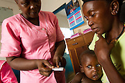 MCH Aide Bridget Mbale Lebbie (C) explains antimarial dosage to Kadiatu Conteh, 35, as she holds her one-year-old boy Nuah Conteh at the Kaniya PHU in the village of Kaniya, Sierra Leone, on Friday April 23, 2010..