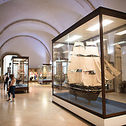 The Museu de Marinha (Maritime Museum of Navy Museum) focuses on Portuguese maritime history. It features exhibits on Portugal's Age of Discovery, the Portuguese Navy, commercial and recreational shipping, and, in a large annex, barges and seaplanes. Located in the Belem neighborhood of Lisbon, it occupies, in part, one wing of the Jerónimos Monastery. Its entrance is through a chapel that Henry the Navigator had built as the place where departing voyagers took mass before setting sail. The museum has occupied its present space since 1963.