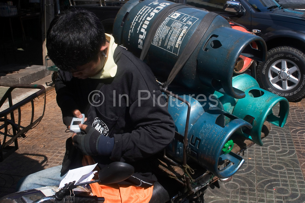 Transport worker carrying three large gas cannisters on his bicycle stops to send a text message on his cell phone, Chinatown, Bangkok.