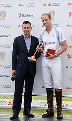Left to right, HRH THE DUKE OF CAMBRIDGE, receives a gift of a miniture polo stick for HRH Prince George of Cambridge from MARTIN SANDER at the Audi Polo Challenge 2013 at Coworth Park Polo Club, Berkshire on 3rd August 2013.