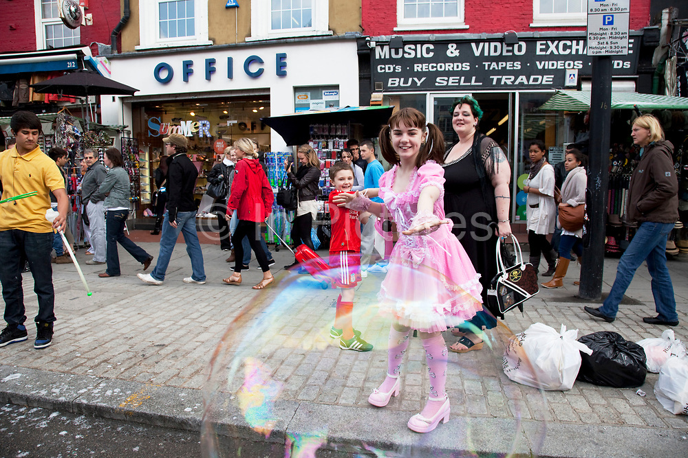 LONDON, ENGLAND, UK, JUNE 11TH 2011. Mother Louise Irwin-Ryan with her daughter Georgia (11, wearing a pink Lolita dress) and son Kiefer (8, wearing a red Liverpool Football Club kit) spending a day out together in Camden Town, North London. The kids here both decide to play on the side of the road trying to burst giant bubbles. Louise is on various benefits to help support her family income, and housing, although recent government changed to benefits may affect her family drastically, possibly meaning they may have to move out of London. Louise Ryan was born on the Wirral peninsula in 1970.  She moved to London with her family in 1980.  Having lived in both Manchester and Ireland, she now lives permanently in North London with her husband and two children. Through the years Louise has battled to recover from a serious motorcycle accident in 1992 and has recently been diagnosed with Bipolar Affective Disorder. (Photo by Mike Kemp/For The Washington Post)