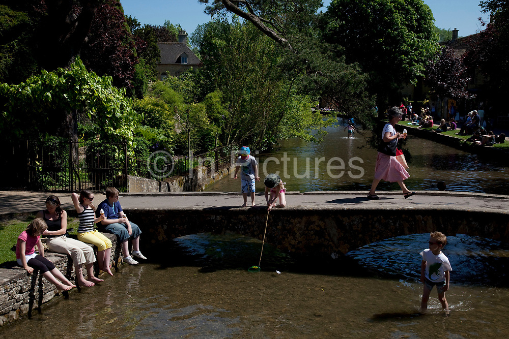 Crowds of visitors and children playing at Bourton-on-the-Water in The Cotswolds, Gloucestershire, UK.  It is known as the 'Venice of the Cotswolds' because of the bridge-spanned stream that runs through the village, this is one of the most popular places to visit in the area. Popular with both the English themselves and international visitors from all over the world, the area is well known for gentle hillsides 'wolds', outstanding countryside, sleepy ancient limestone villages, historic market towns and for being so 'typically English' where time has stood still for over 300 years. Throughout the Cotswolds stone features in buildings and stone walls act as a common thread in seamlessly blending the historic towns & villages with their surrounding landscape. One of the most 'quintessentially English' and unspoiled regions of England.