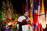 Middletown, New York - A priest speaks on the stage as members of St. Joseph's Church celebrate the Festival of Nuestra Senora de Guadalupe in the church gymnasium on Saturday, Dec. 14, 2013.