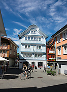 Bicyclist. Frescoes decorate buildings in Appenzell village, in Switzerland, Europe. Appenzell Innerrhoden is Switzerland's most traditional and smallest-population canton (second smallest by area).