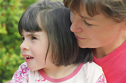Mother sitting behind young girl with autism,