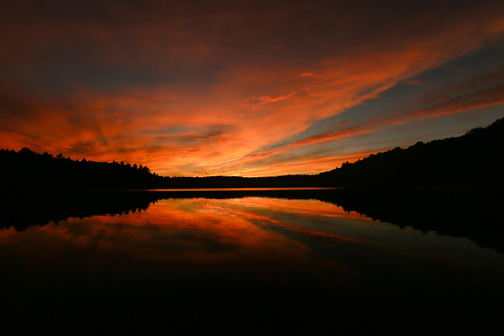 A glowing autumn sunset reflecting in the calm waters of Walden Pond.
