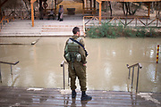 An Israeli soldier is standing on the bank of the Jordan River  at the Qasr el Yahud (Arabic for:  the Castle of the Jews) baptism site in the Jordan River Valley, near the West Bank city of Jerico.