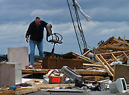 5/23/04 Hallam Neb, Curtis Schwaninger picks up a chair from the ruins in the his and his wife, Joetta's, house about 1/2 mile east of Hallam, Neb. <br /> The Schwaninger's house was destroyed while they were at a graduation in Lincoln Neb. The Schwaningers have had the house about nine years.  (Photo by Chris Machian/Machian Photo)