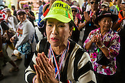 17 FEBRUARY 2014 - BANGKOK, THAILAND:  An anti-government protestor greets Ministry of Education workers while protestors march through the portico of the Ministry of Education in Bangkok. The anti-government protest movement, led by the People's Democratic Reform Committee and called Shutdown Bangkok has been going on for more than a month. The protest movement called, the People's Democratic Reform Committee (PDRC), wants to purge the current ruling party and its patrons in the Shinawatra family from Thai politics. The movement has consistently refused any dialogue or negotiations with the Pheu Thai ruling party. Over the weekend Thai police claimed to have taken the protest areas around Government House (the Prime Minister's office) away from protestors but on Monday protestors marched unimpeded to Government House and retook the area.  PHOTO BY JACK KURTZ