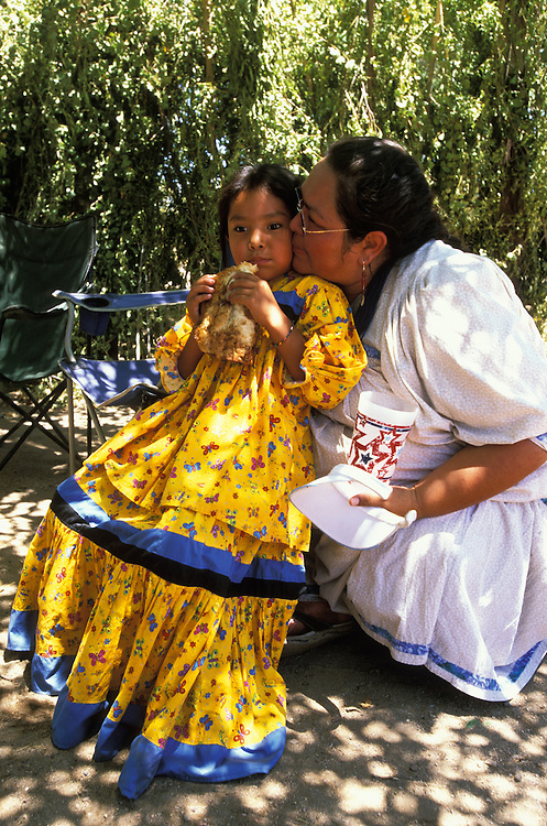 An Apache mother and daguhter in intimate conversation at a meal break during a Sunrise Dance, the first menstruation rite of an Apache girl, on the San Carlos Apache Indian Reservation in Arizona, USA. They are both dressed in camp dresses.