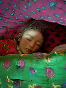 Rani Boi's grand child sleeping in Kyrgyz fabric. Rani Boi is the chief of the last yurt camp in the Little Pamir - the summer camp of Qoqtruq, near the China/Tajikistan border.<br /> <br /> Adventure through the Afghan Pamir mountains, among the Afghan Kyrgyz and into Pakistan's Karakoram mountains. July/August 2005. Afghanistan / Pakistan.