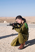 Israeli young female soldier in uniform aiming her M16 rifle