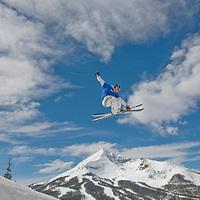 SKIING, Big Sky, Montana. Ben Wiltsie (MR) skis aerial manouvers in half pipe in terrain park at Big Sky Ski Resort, near Bozeman, Montana. 11,166-foot Lone Mountain is in bkg.