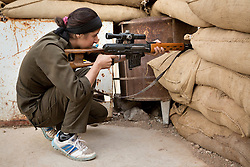 © Licensed to London News Pictures. 28/09/2014. Rabia, Iraq. A female sniper belonging to the Syrian-Kurdish YPJ takes aim at what she thinks may be an Islamic State sniper changing position in the Iraqi border town of Rabia.<br /> <br /> Facing each other across the Iraq-Syria border, the towns of Al-Yarubiyah, Syria, and Rabia, Iraq, were taken by Islamic State insurgents in August 2014. Since then The town of Al-Yarubiyah and parts of Rabia have been re-taken by fighters from the Syrian Kurdish YPG. At present the situation in the towns is static, but with large exchanges of sniper and heavy machine gun fire as well as mortars and rocket propelled grenades, recently occasional close quarter fighting has taken place as either side tests the defences of the other. Photo credit: Matt Cetti-Roberts/LNP