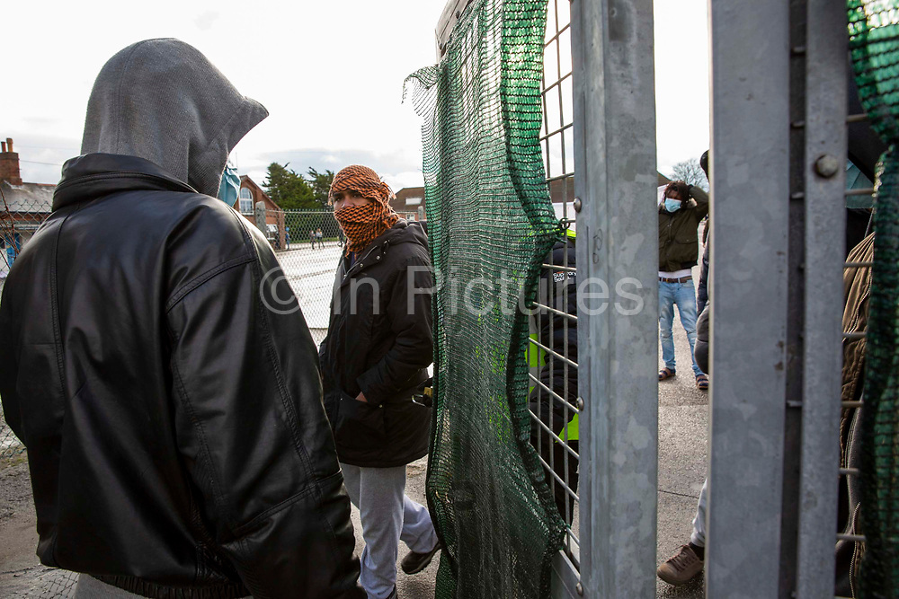 A young male Asylum seeker using the only entrance to get inside Napier Barracks on the 12th of January 2021, Folkestone, United Kingdom. Over 400 asylum seekers are being kept at Napier Barracks in unsuitable, cold accommodation, they are experiencing mental health issues as well as being vulnerable to health conditions including COVID-19.