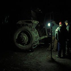 Members of the Federal Hocking high school Future Farmers of America (FFA) Club study tractor engines by the light of a shop-lamp at one member's farm in southeast Ohio.