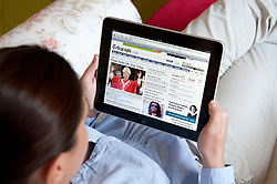 Woman using iPad tablet computer to read The Daily Telegraph UK newspaper