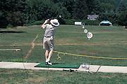 man practicing swing at driving range