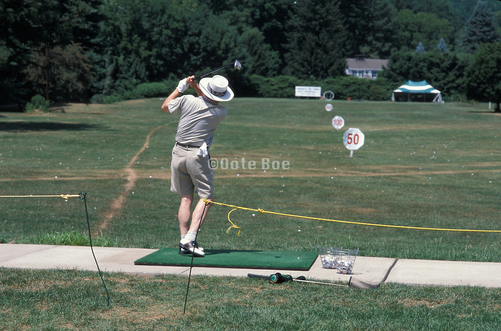 man practicing swing at driving range
