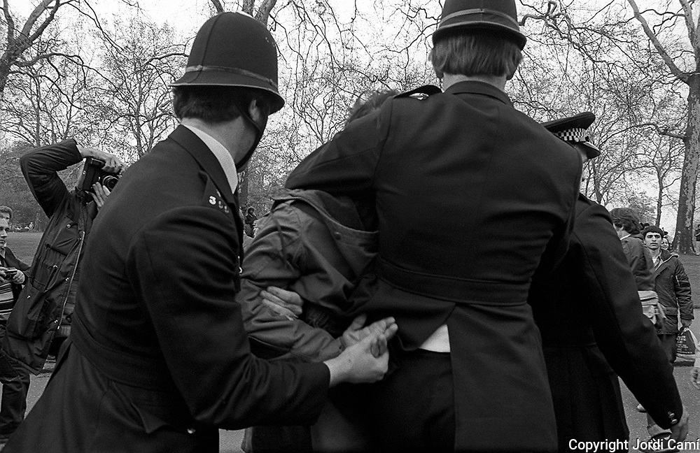 Two policemen detain a pro Khomeini protester in front of the Iranian Embassy during the six day siege and hostage crisis.  South Kensington, London, 1th May 1980.