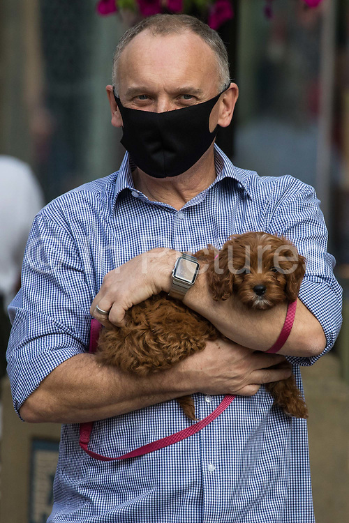 A man holding a small dog in his arms wears a face covering to help prevent the spread of the coronavirus on 20 September 2020 in Staines-Upon-Thames, United Kingdom. The Borough of Spelthorne, of which Staines-upon-Thames forms part along with Ashford, Sunbury-upon-Thames, Stanwell, Shepperton and Laleham, has been declared an 'area of concern' for COVID-19 by the government following a marked rise in coronavirus infections which is inconsistent with other areas of Surrey.