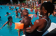 A 1990s Afro-Caribbean mother and her child enjoy the August heatwave in the unheated waters of the Grade II listed  Brockwell (Brixton) Lido in Brockwell Park, Herne Hill, 25th August 1995, in London, England. The Lido is an oasis for city dwellers to escape, if only for an hour from the pressures of fast urban life. Brockwell Lido is a large, open air swimming pool in Brockwell Park, Herne Hill, London. It opened in July 1937, closed in 1990 but after a local campaign was re-opened in 1994. Brockwell Lido was designed by HA Rowbotham and TL Smithson of the London County Council's Parks Department to replace Brockwell Park bathing pond. (Photo by Richard Baker / In Pictures via Getty Images)