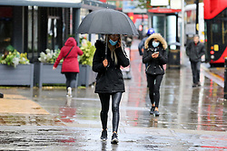 © Licensed to London News Pictures. 03/11/2020. London, UK. A woman wearing a face covering shelters from rainfall underneath an umbrella in north London. The Met Office forecasts rain and strong winds in the South East of England. Photo credit: Dinendra Haria/LNP