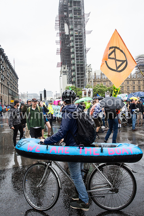 London, UK. 19 July, 2019. Climate activists from Extinction Rebellion arrive in Parliament Square on a march from their camp at Waterloo Millennium Green on the fifth day of their 'Summer uprising' to call on local and central government to take urgent steps to address the climate emergency.