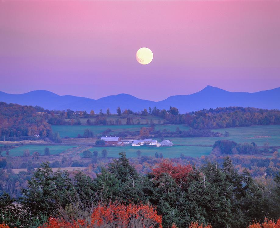 Full moon rises over Jay Peak & hillside farm in fall, Franklin, VT