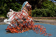 In the UK, 32,313 people have now died after testing positive for coronavirus which is now the highest death toll in Europe, even exceeding that of Italy. With UK lockdown continuing with social distancing measures still in effect, a childrens' playground rocking horse is wrapped and tangled in construction netting in Lucas Gardens, a small public space in Southwark, south London, on 5th May 2020, in London, England.